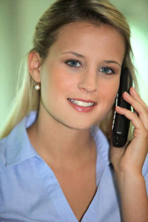 Blond office worker making phone call photo