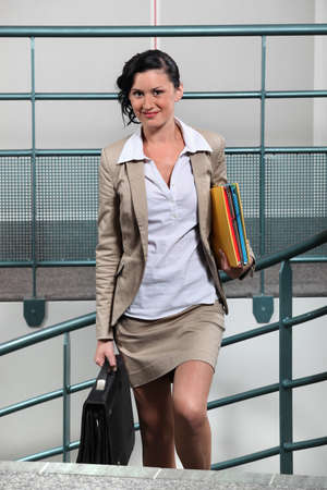 young businesswoman with briefcase going upstairs photo