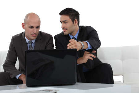 Businessmen looking at a laptop Stock Photo - 13621796