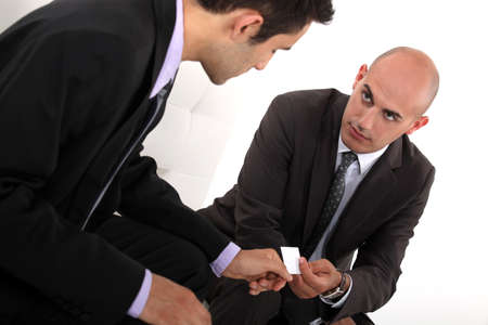 Businessmen exchanging cards photo