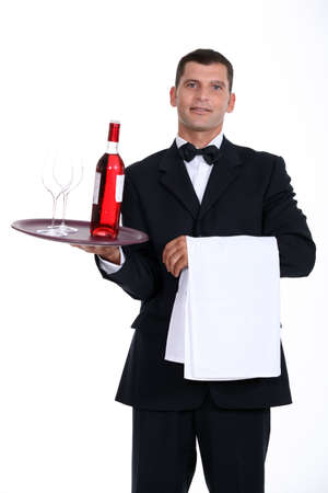 Waiter holding bottle of wine and glasses on tray photo