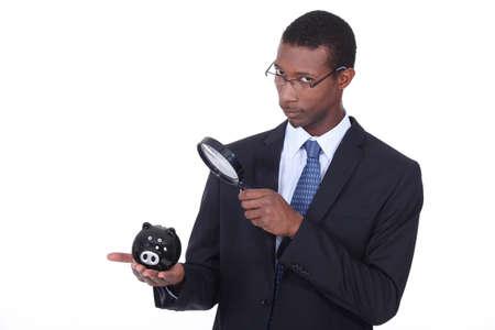 fondos negocios: Hombre africano mirando una hucha a trav�s de una lupa Foto de archivo