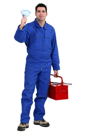 coveralls: Workman holding up banknotes Stock Photo