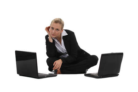 Businesswoman sat on the floor with two laptops photo