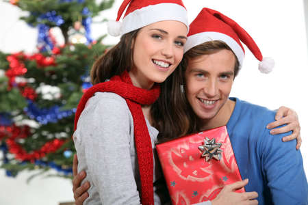 Couple sat by Christmas tree Stock Photo - 13622185