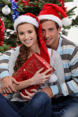 Couple by a Christmas tree photo
