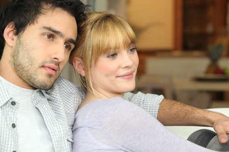 pareja viendo television: Pareja joven viendo la televisión en su casa