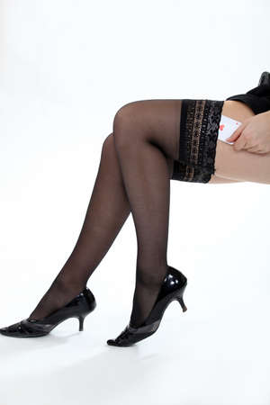 Woman sliding playing card into tights Stock Photo - 13621889