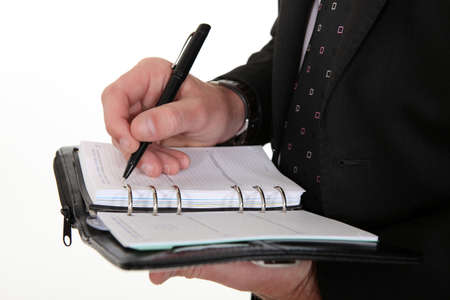 noting: businessman noting down appointment on agenda Stock Photo