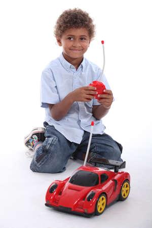 ひざまずく: 車をしている少年