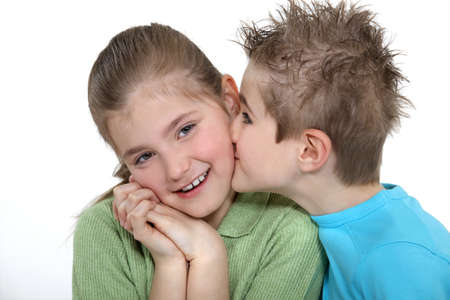 cheek to cheek: Boy kissing a girl on the cheek Stock Photo
