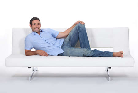 lie down: Barefoot man lying on a couch