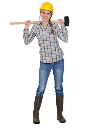 over shoulders: Woman posing with sledge-hammer over shoulders Stock Photo
