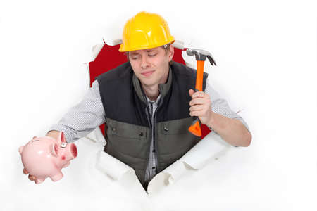 Construction worker with a hammer and piggy bank photo