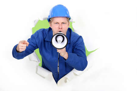 desperate face: craftsman shouting through a megaphone Stock Photo