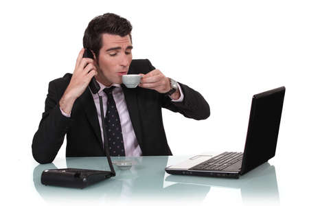 Businessman having a coffee at his desk Stock Photo - 13621808