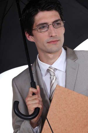 sheltering: Businessman with folder sheltering from rain Stock Photo