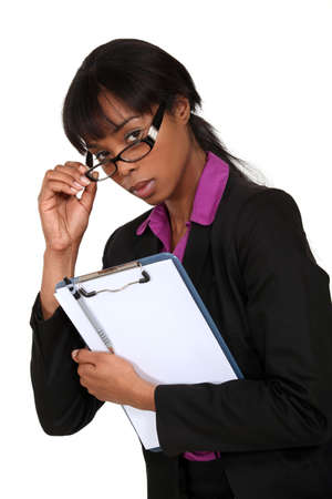 intimidating: portrait of intimidating black businesswoman with glasses lowered holding clipboard Stock Photo