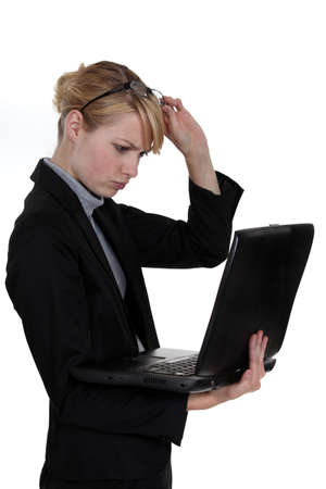 cute blonde businesswoman with laptop frowning with glasses raised