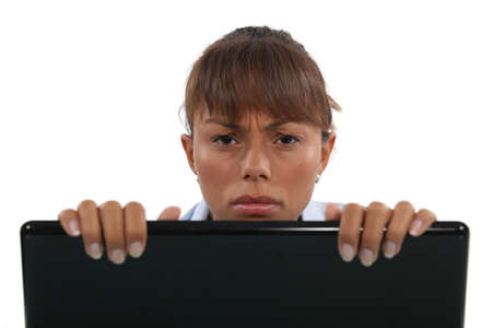 displeased: Displeased businesswoman peering over laptop Stock Photo
