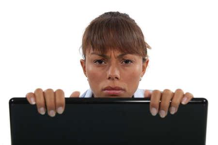 Displeased businesswoman peering over laptop Stock Photo - 13621734