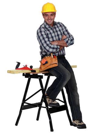 workbench: Relaxed carpenter next to a workbench