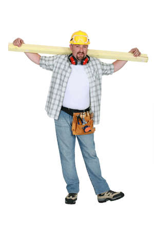 A carpenter holding a plank  photo