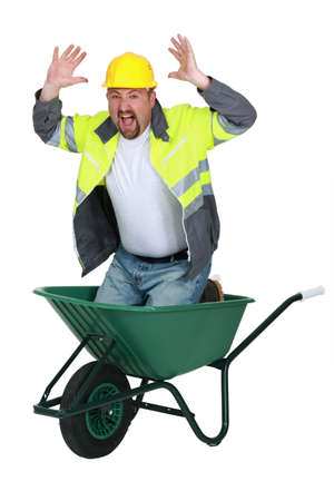 Laborer sitting in a wheelbarrow screaming photo