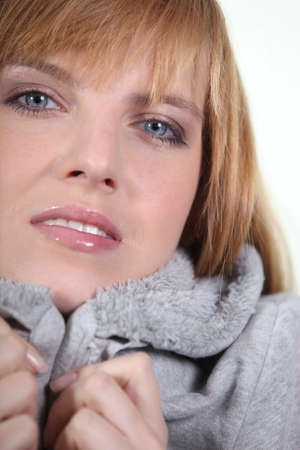Woman in makeup and a snug grey hooded sweatshirt photo