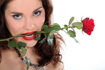 Woman holding a rose in her mouth photo