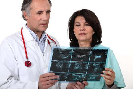 medical scanner: doctor and nurse examining a scanner image