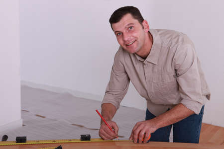 Tradesman marking a measurement on a wooden plank Stock Photo - 13645695