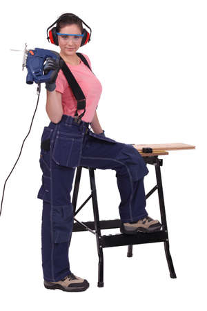 Women with a chainsaw cutting wood Stock Photo