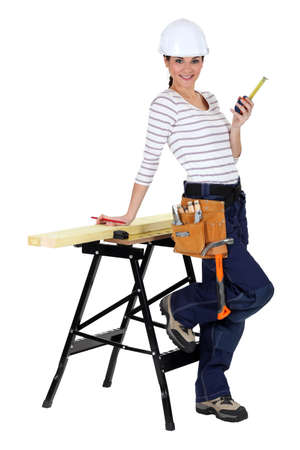 takes: Female construction worker with a workbench