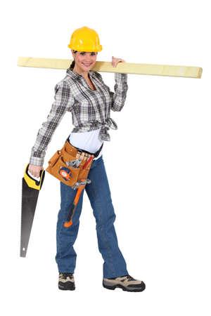 serrucho: Carpintero Mujer llevando tabla de madera Foto de archivo