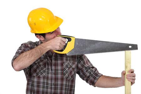 serrucho: Un carpintero con una sierra de mano Foto de archivo