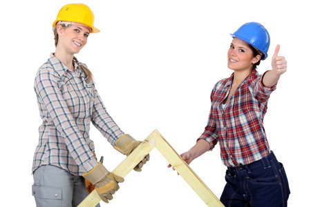 Two women with wooden truss photo