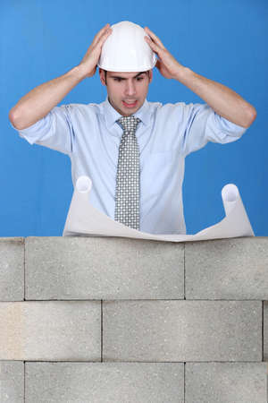 Stressed architect reviewing plans Stock Photo - 13645853