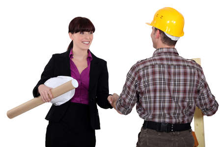 clinch: Businesswoman greeting a construction worker Stock Photo