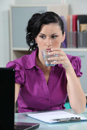 Brunette office worker drinking glass of water photo