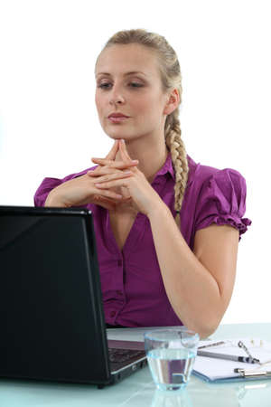 Woman thinking at her laptop photo