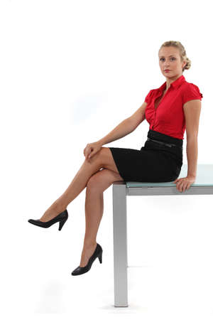 Attractive blond sat on desk Stock fotó