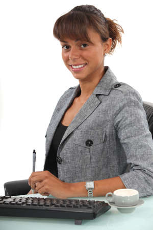 Smiling businesswoman sitting at her desk Stock Photo - 13645831