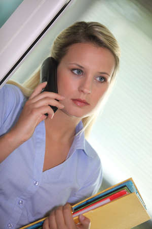 straight faced: Office clerk answering the telephone