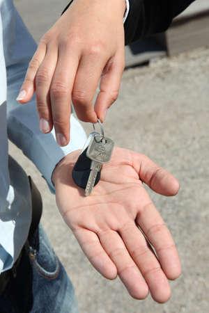Saleswoman handing key to man photo