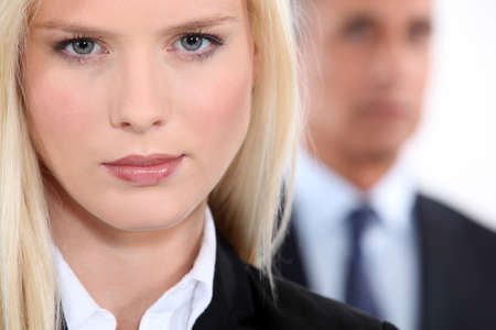 Pretty blonde woman in a suit with an older man out of focus in the background Stock Photo - 13645715