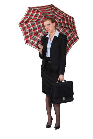 unfriendly: Austere businesswoman holding a briefcase and an umbrella
