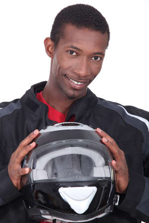 man in a racing suit holding a helmet
