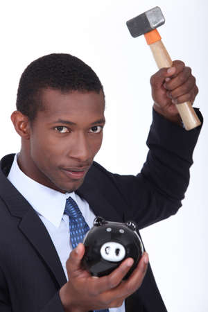 whack: Man about to break open a piggy bank with a hammer Stock Photo