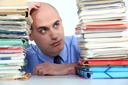 Office worker looking at stacks of files Stock Photo - 13645763